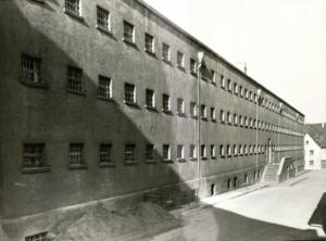 Dargestellt ist die schwarz-weis Fotografie der ehemaligen Haftanstalt in Karlsruhe-Durlach. Drei Reihen viereckiger Fenster, die mit Eisengittern versperrt sind, bilden eine triste Fassade die nur durch vertikale Regenrinnenrohe unterbrochen sind. Die Gefängnisfront scheint symmetrisch aufgebaut zu sein, in der Mitte befindet sich das Eingangsportal zu welchen ein zweitseitiger Treppenaufgang hinaufführt.